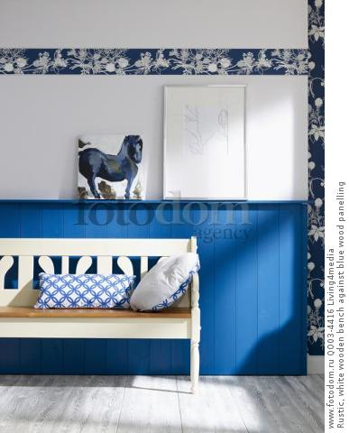 Rustic, white wooden bench against blue wood panelling