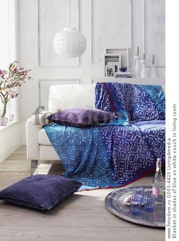 Blanket in shades of blue on white couch in living room