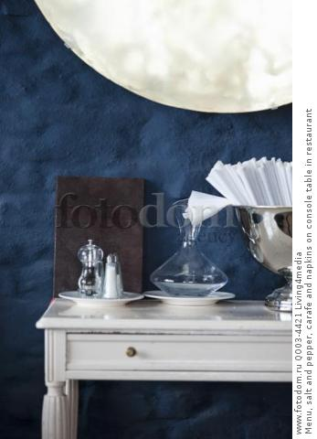 Menu, salt and pepper, carafe and napkins on console table in restaurant