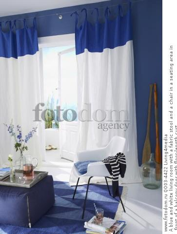 A blue and white living room with a fabric stool and a chair in a seating area in front of a balcony door with floor-length curt
