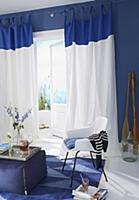 A blue and white living room with a fabric stool a