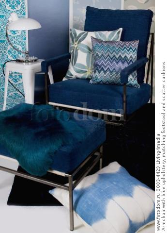 Armchair with blue upholstery, matching footstool and scatter cushions