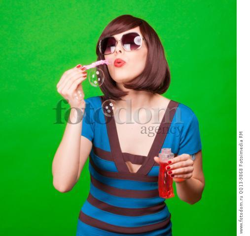 Beautiful young sexy pin-up girl with surprised expression, on green background