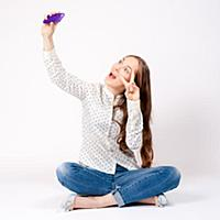 Happy young woman taking a selfie using her smartp