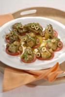 Козий сыр в виноградных листьях с томатами и оливк