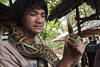 (6/19/2017)  A tourist takes pictures with a boa s