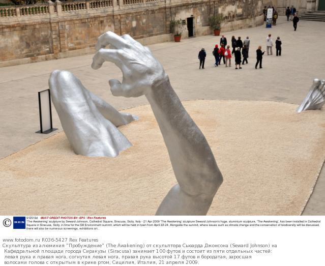Скульптура из алюминия 'Пробуждение' (The Awakening) от скульптора Сьюарда Джонсона (Seward Johnson) на Кафедральной площади города Сиракузы (Siracusa) занимает 100 футов и состоит из пяти отдельных частей: левая рука и правая нога, согнутая левая нога, правая рука высотой 17 футов и бородатая, заросшая волосами голова с открытым в крике ртом, Сицилия, Италия, 21 апреля 2009.