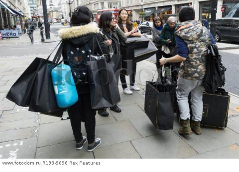 Mandatory Credit: Photo by Ray Tang/REX Shutterstock (5346899ah) Customers with their purchased clothes outside the Oxford Circus store Balmain x H&M launch, London, Britain - 05 Nov 2015