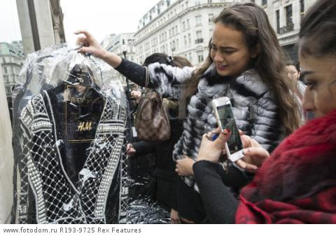 Mandatory Credit: Photo by Ray Tang/REX Shutterstock (5346899o) Customers with their purchased clothes outside the Regent Street store Balmain x H&M launch, London, Britain - 05 Nov 2015