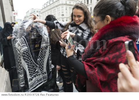 Mandatory Credit: Photo by Ray Tang/REX Shutterstock (5346899p) Customers with their purchased clothes outside the Regent Street store Balmain x H&M launch, London, Britain - 05 Nov 2015