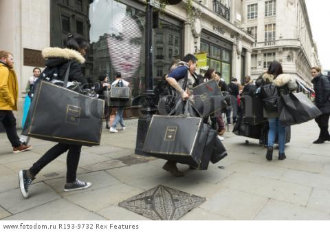 Mandatory Credit: Photo by Ray Tang/REX Shutterstock (5346899v) Customers with their clothes bags outside the  Regent Street store Balmain x H&M launch, London, Britain - 05 Nov 2015