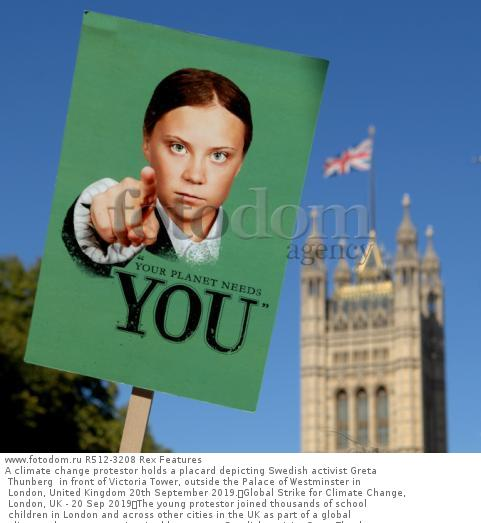 A climate change protestor holds a placard depicting Swedish activist Greta Thunberg  in front of Victoria Tower, outside the Palace of Westminster in London, United Kingdom 20th September 2019. Global Strike for Climate Change, London, UK - 20 Sep 2019 The young protestor joined thousands of school children in London and across other cities in the UK as part of a global climate change protest inspired by teenage Swedish activist Greta Thunberg