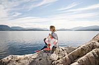 Woman sitting on rock by sea with kite