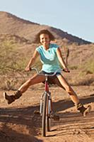 Woman on bicycle in desert landscape