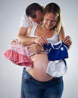 pregnant man and woman with baby clothes
