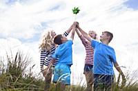 Four friends holding pinwheel, Wales, UK