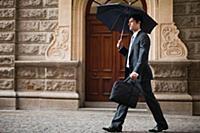 Businessman carrying umbrella on street