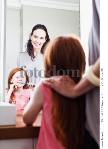 Mother watching daughter brush teeth