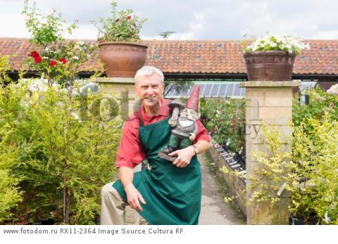 Gardener with garden gnome in nursery