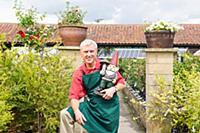 Gardener with garden gnome in nursery