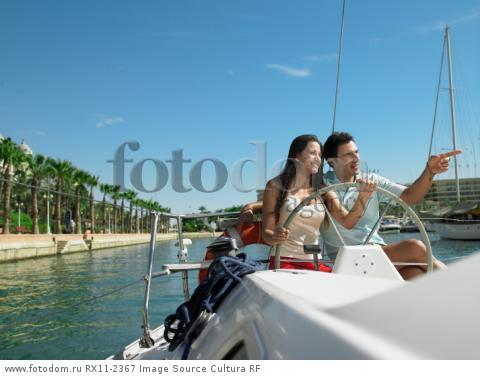 Young couple at wheel of yacht in marina