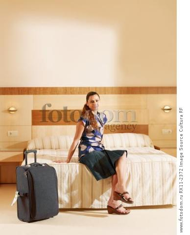 Woman sitting on hotel bed by luggage