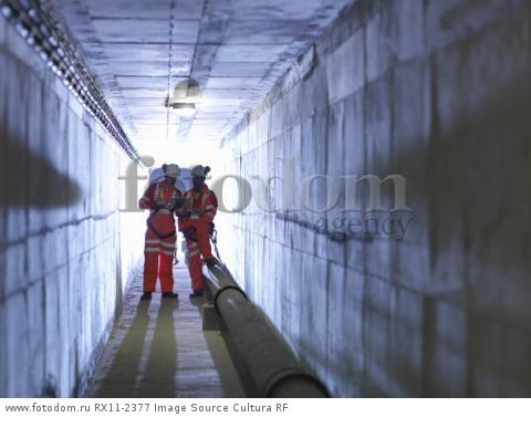 Civil engineers in discussion in tunnel of suspension bridge. The Humber Bridge, UK, built in 1981 was the world's largest single-span suspension bridge