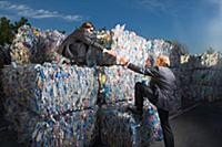 Businessmen climbing a wall of recycling