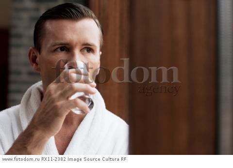 Man in bathrobe drinking water by window