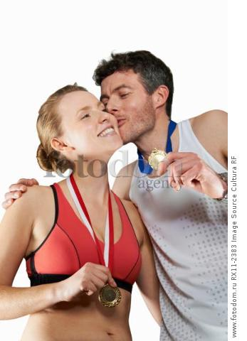 Couple in running gear wearing medals