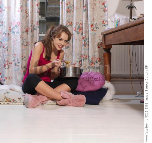 Young woman eating from cooking pot