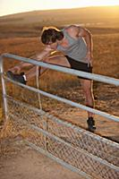 Man stretching on fence in rural field
