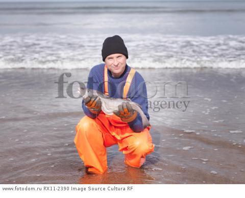 Fisherman on shore holding fish