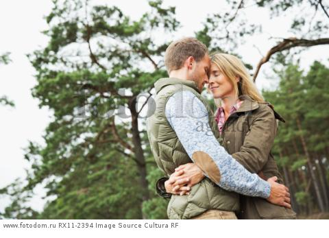 Mid adult couple hugging in forest