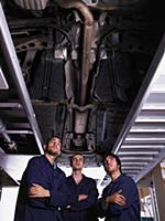 Three mechanics standing under a car