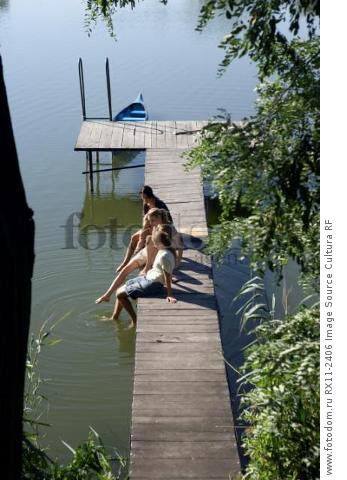 Three young women on a pier.