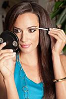 A brunette woman holding a compact mirror and appl