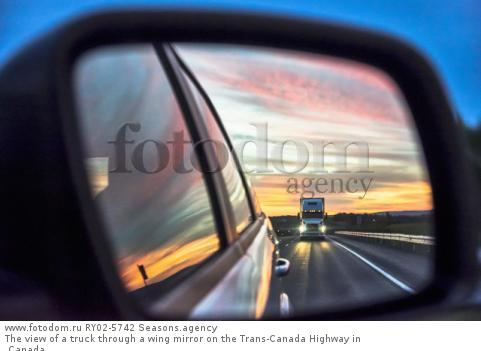 The view of a truck through a wing mirror on the Trans-Canada Highway in Canada