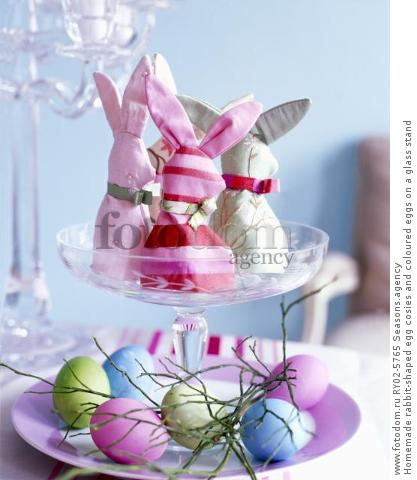 Homemade rabbit-shaped egg cosies and coloured eggs on a glass stand