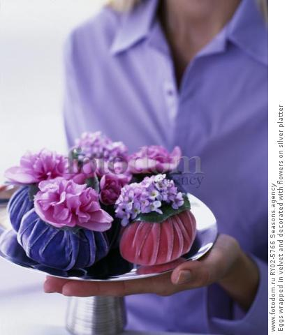 Eggs wrapped in velvet and decorated with flowers on silver platter