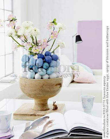 A glass container filled with blue Easter eggs, sprigs of blossom and buttercups