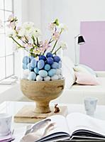 A glass container filled with blue Easter eggs, sp