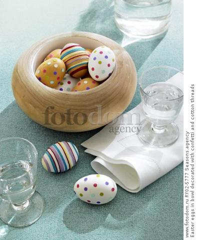Easter eggs in bowl decorated with confetti and cotton threads