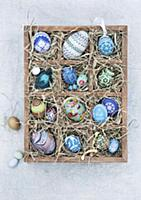 Blue, hand-painted Easter eggs in a wooden seedlin
