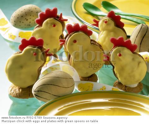 Marzipan chick with eggs and plates with green spoons on table