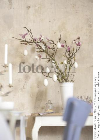 Easter eggs hanging on branches in white vase