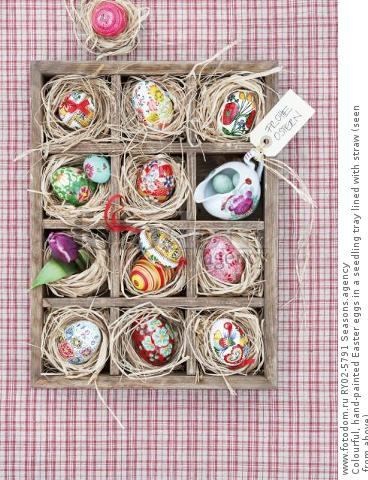 Colourful, hand-painted Easter eggs in a seedling tray lined with straw (seen from above)