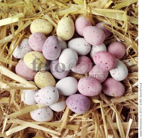 Colourful chocolate mini eggs resting in straw