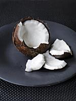Opened coconut on black plate