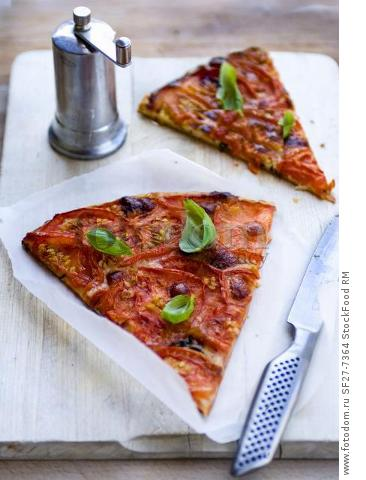 Two slices tomato tart with basil and pepper mill